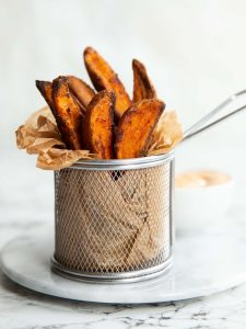 wedges in a small fry container on marble board with dip blurred in background