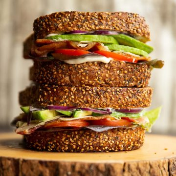 one sandwich stacked on top of each other on wooden board