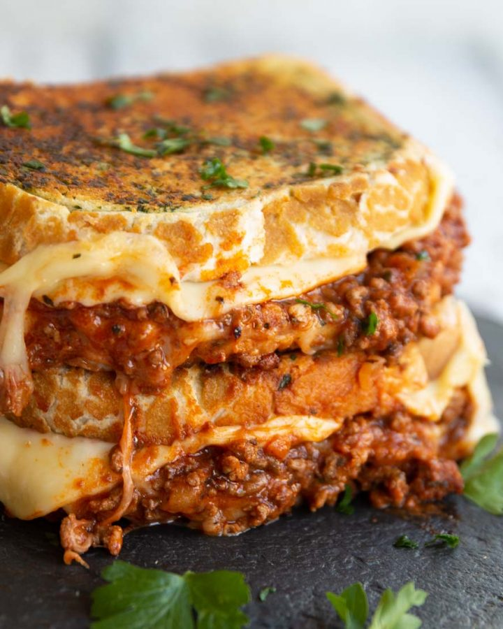 two sandwiches stacked on each other with bolognese and cheese spilling out