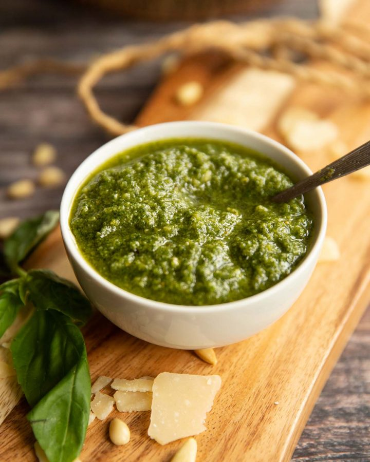 pesto in a small white pot on wooden chopping board