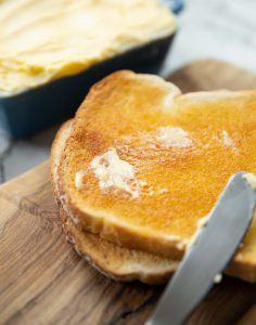 smudge of butter melting into slice of toast on chopping board