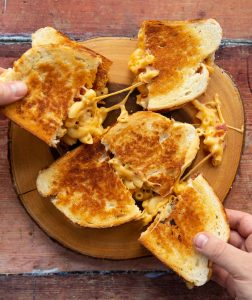 overhead shot of grilled cheese on wooden board with hands pulling them off cheese spilling out