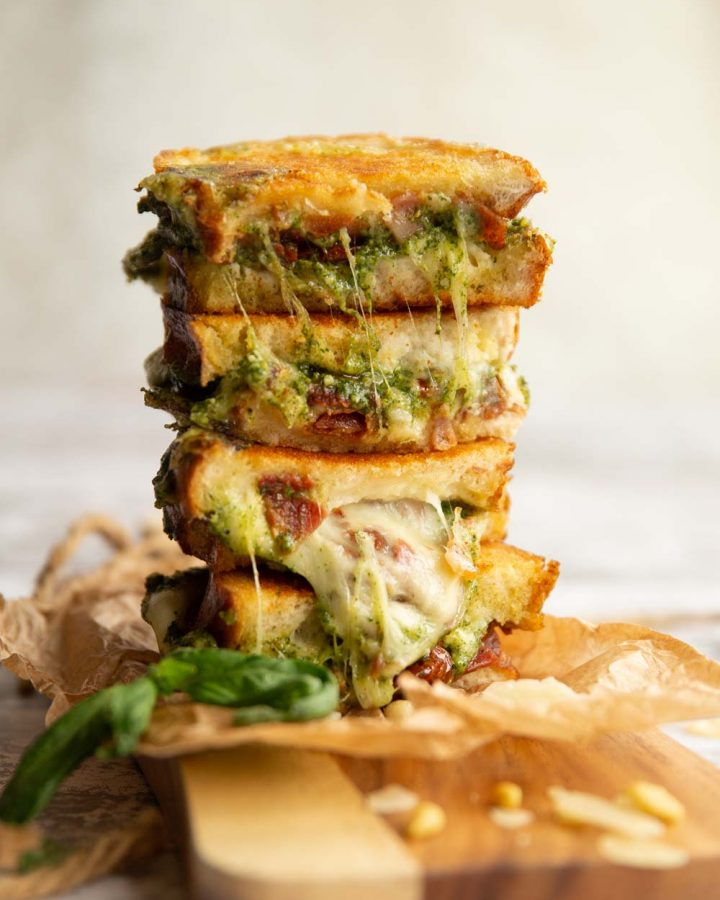 4 sandwich halves stacked on top of each other with pesto and cheese spilling out