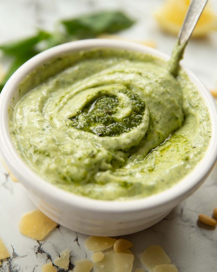 pesto mayo in small white pot surrounded by garnish with teaspoon dunked in