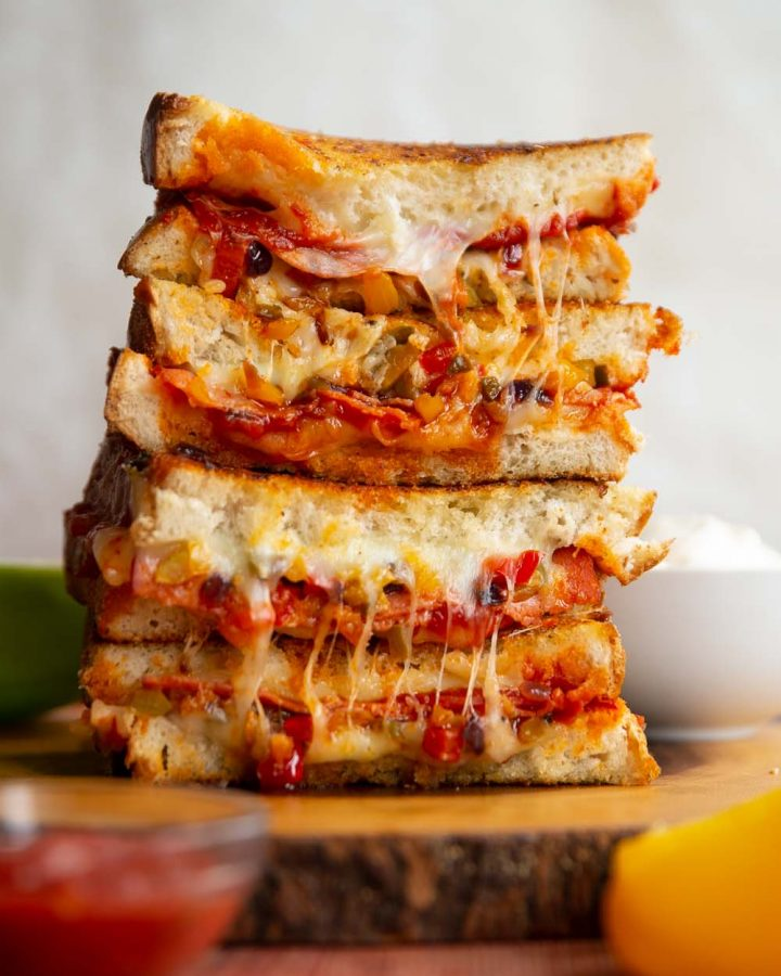 4 sandwich halves stacked on each other with cheese and filling spilling out
