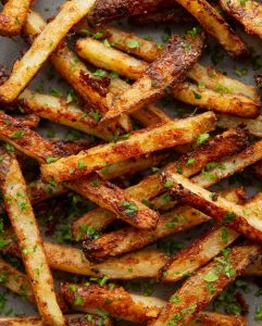 overhead shot of fries fresh out the oven garnished with parsley