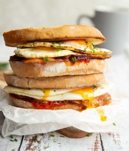 two sandwiches stacked on each other with yolk dripping down and mug blurred in background