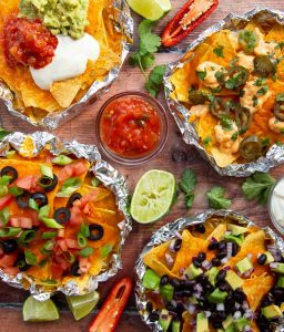 overhead shot of 4 foil pack nachos with limes, coriander and chilli to garnish