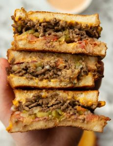 overhead shot of 3 sandwich halves showing filling above marble background