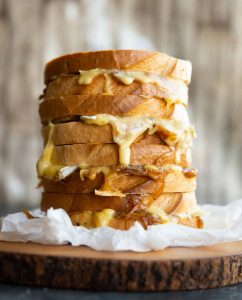 4 grilled cheeses stacked on each other on wooden board with cheese dripping out