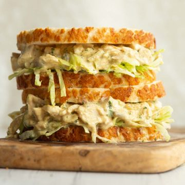 two coronation chicken sandwiches stacked on a wooden board