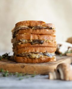 3 sandwiches stacked on each other on wooden board surrounded by mushrooms and thyme
