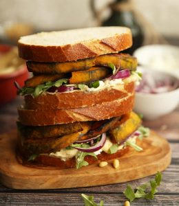 two sandwiches stacked on each other on wooden board with ingredients blurred in background