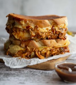 two sandwiches stacked on wooden board with cheese and chicken spilling out