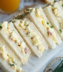 egg mayo tea sandwiches across wooden board