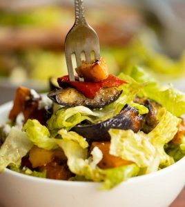 closeup shot of silver fork digging into small bowl of salad