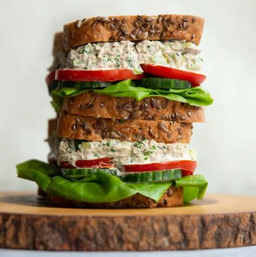 2 sandwiches stacked on each other on wooden board
