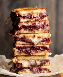 4 sandwich halves stacked on each other with brie and blackberries spilling out