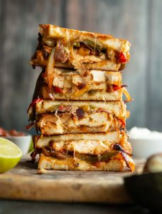 4 sandwich halves stack on each other with filling spilling out on wooden board