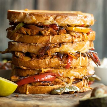 3 sandwiches stacked on each other with filling spilling out on wooden board