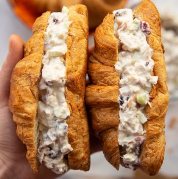 overhead shot of hand holding two croissant sandwiches