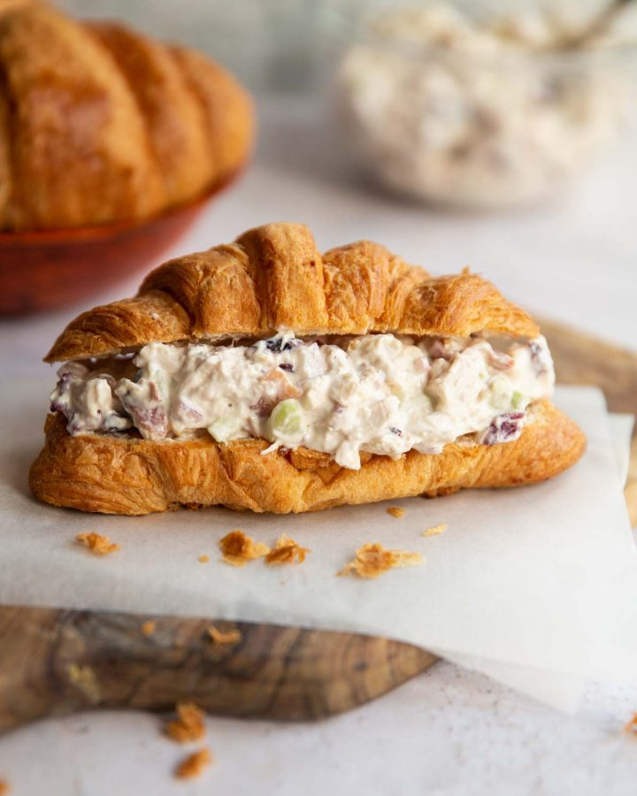 croissant sandwich on wooden board with croissants and chicken salad blurred in background