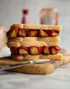 two sandwiches stacked on each other on wooden board with ketchup, vinegar and bread blurred in background