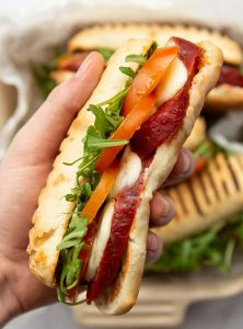 overhead close up shot of hand holding chorizo sandwich above 3 sandwiches in dish