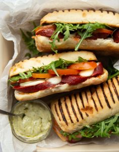 overhead shot of 3 sandwiches in dish with pesto mayo