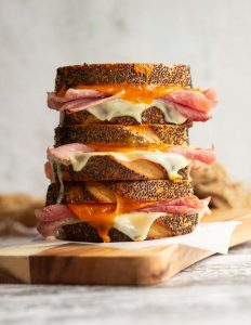 3 sandwiches stacked on each other with ham and cheese dripping out on wooden board