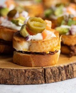 close up shot of mini sandwich on wooden board with more blurred in the background