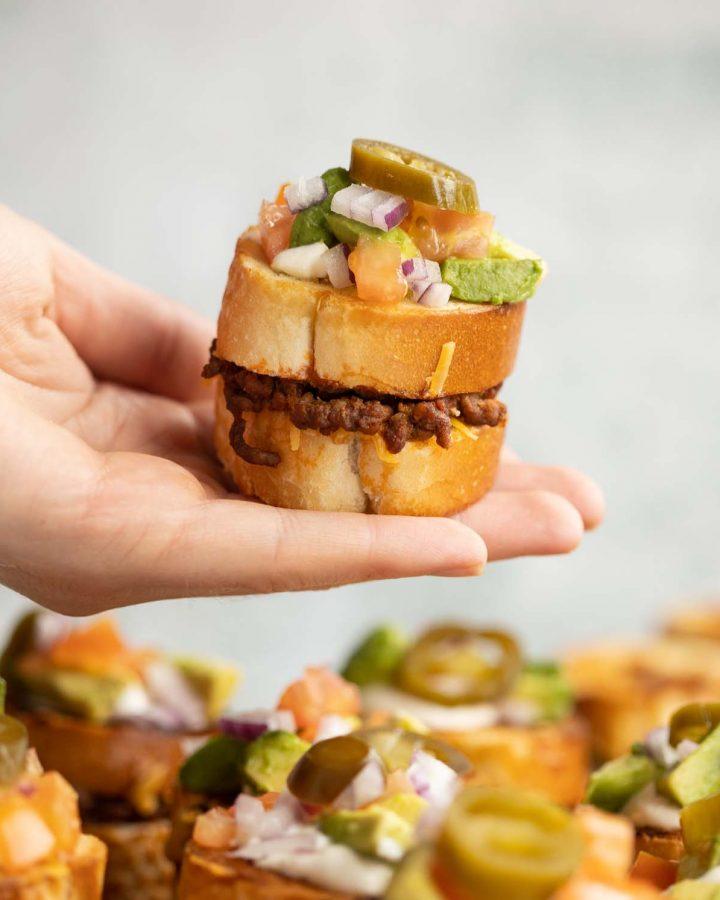 hand holding mini sandwich above board of sandwiches