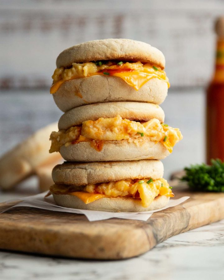 3 sandwiches stacked on each other on wooden board with muffins, chives and hot sauce blurred in background
