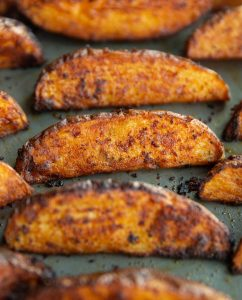 closeup shot of potato wedges fresh out the oven on baking tray