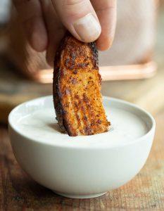 dunking a potato wedge into small white pot of dip