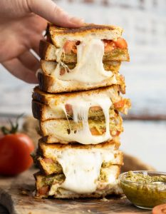 4 sandwich halves stack on each other on wooden board with hand grabbing the top one
