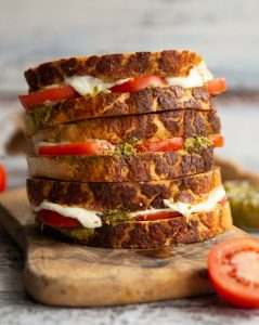 3 sandwiches stacked on each other with tomato, mozzarella and pesto spilling out