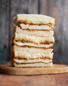 3 sandwich thirds stacked on each other on small wooden board