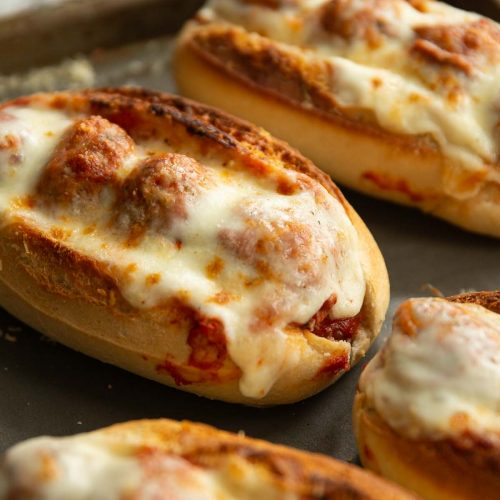 close up shot of meatball sub on oven tray surrounded by 4 others