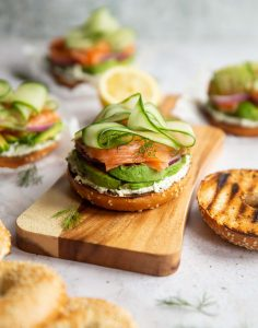 open top salmon bagel on wooden chopping board