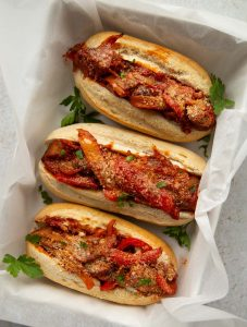 overhead shot of 3 sausage pepper sandwiches in large baking dish garnished with fresh parsley