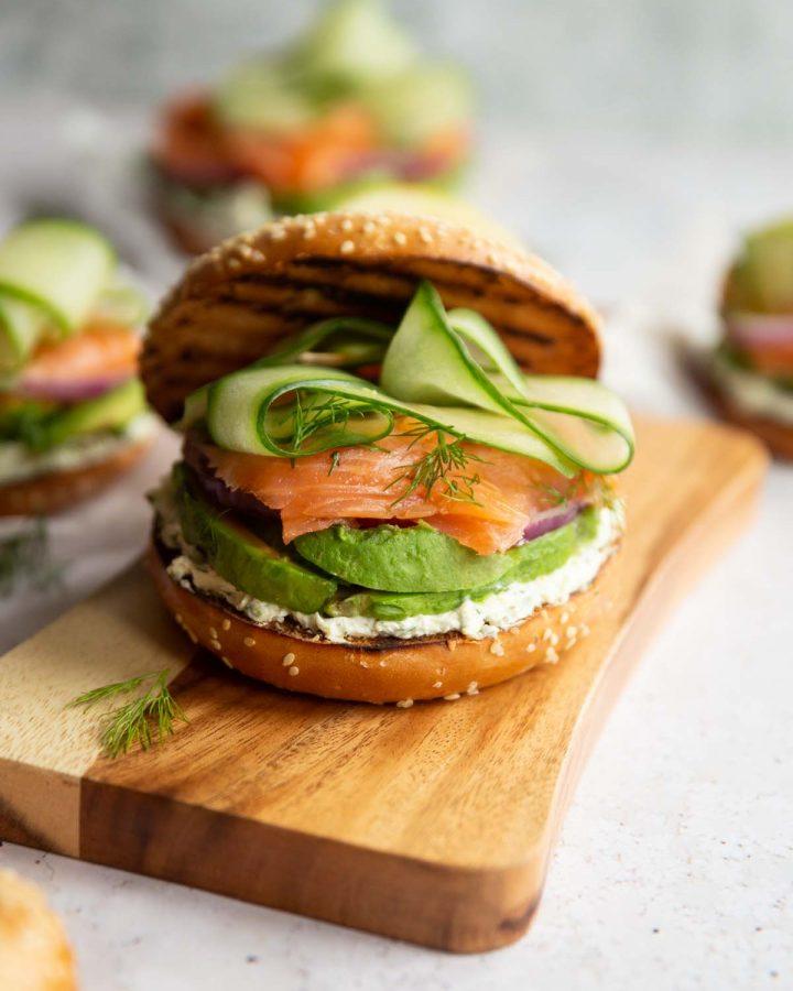 bagel sandwich on chopping board with 3 others blurred in background
