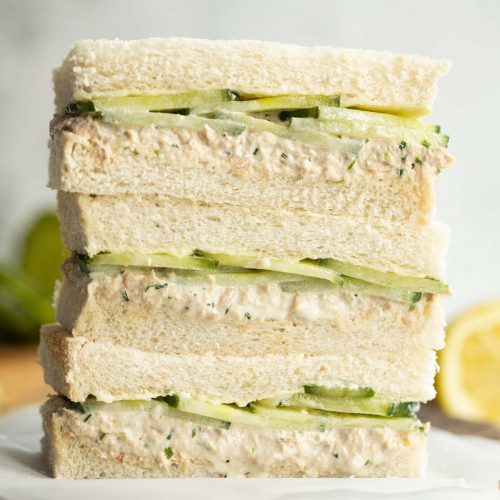 3 finger sandwiches stacked on each other on wooden board with lemon and cucumber blurred in background