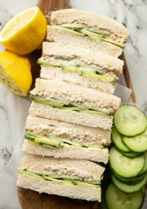 overhead shot of finger sandwiches showing filling on chopping board with lemon and cucumber