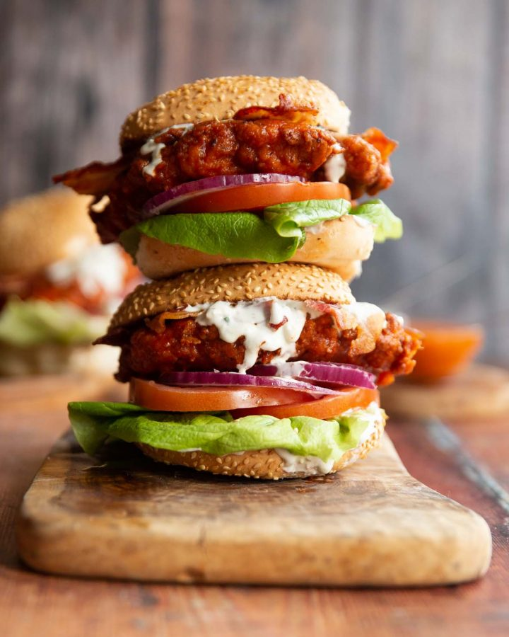 two chicken sandwich stacked on each other on wooden chopping board with blue cheese sauce dripping out