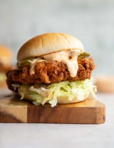 chicken sandwich on wooden board with sauce dripping out