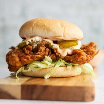 chicken sandwich on wooden board with dip blurred in background