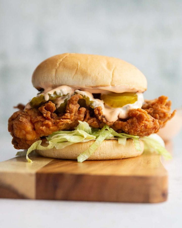 chicken sandwich on wooden board with dip blurred in background