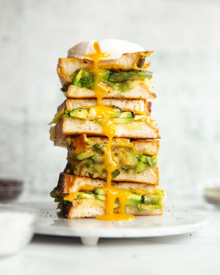 3 sandwich halves stacked on each other on small marble plate