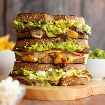3 sandwiches stacked on each other with guac, cotija and chips blurred in background